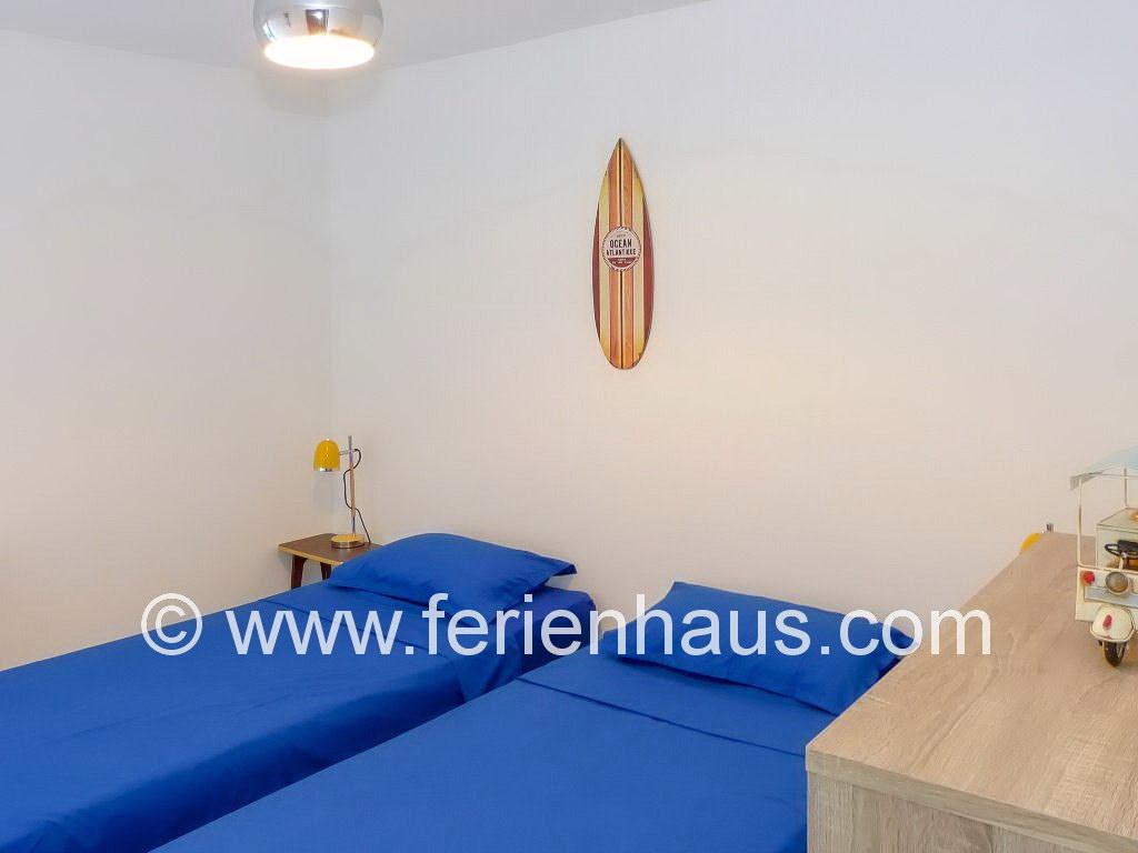 Schlafzimmer mit Einzelbetten im Gartengeschoss des Ferienhauses